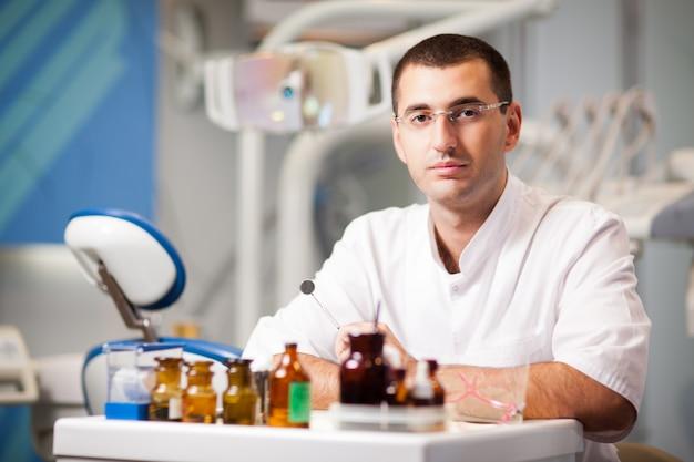 Jovem médico dentista homem de uniforme, sentado perto da cadeira odontológica no consultório odontológico na clínica com equipamentos no fundo
