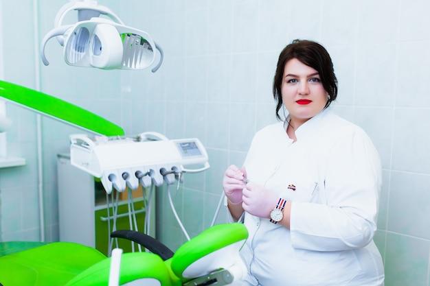 Jovem médico dentista profissional em um escritório moderno com equipamentos odontológicos. o conceito de seguro saúde e atendimento odontológico gratuito. próteses e instalação de folheados.