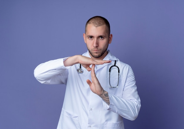 Jovem médico descontente usando túnica médica e estetoscópio no pescoço, fazendo gesto de tempo limite isolado no fundo roxo com espaço de cópia