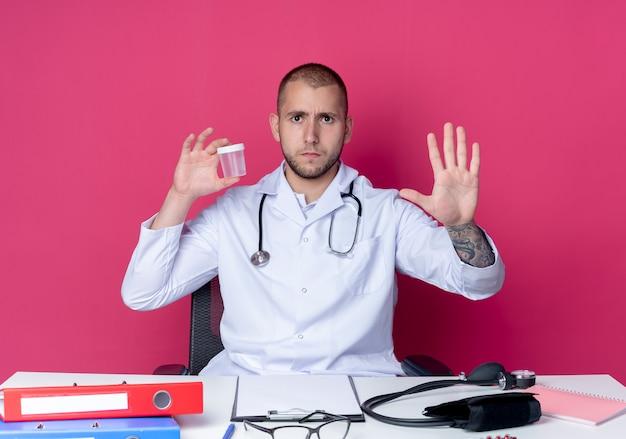 Jovem médico descontente vestindo túnica médica e estetoscópio sentado na mesa com ferramentas de trabalho, segurando um copo médico e mostrando cinco com a mão isolada no fundo rosa