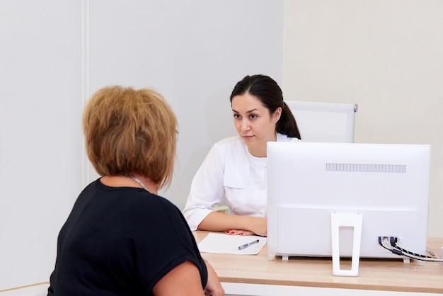 Jovem médico discute com um paciente em uma clínica.