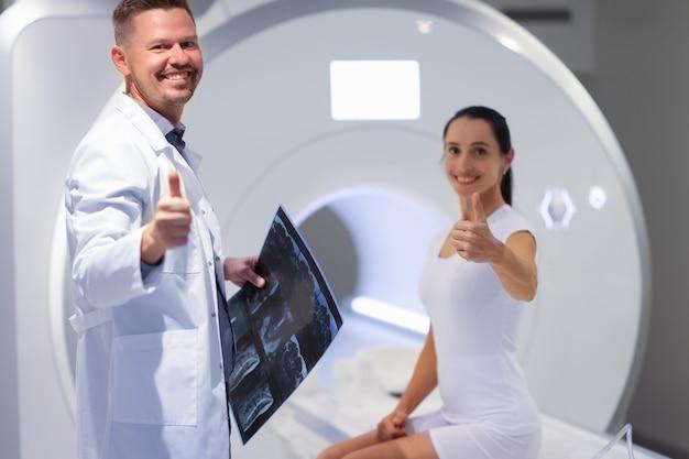 Jovem médico e paciente segurando o polegar na sala de ressonância magnética da sala de ressonância magnética