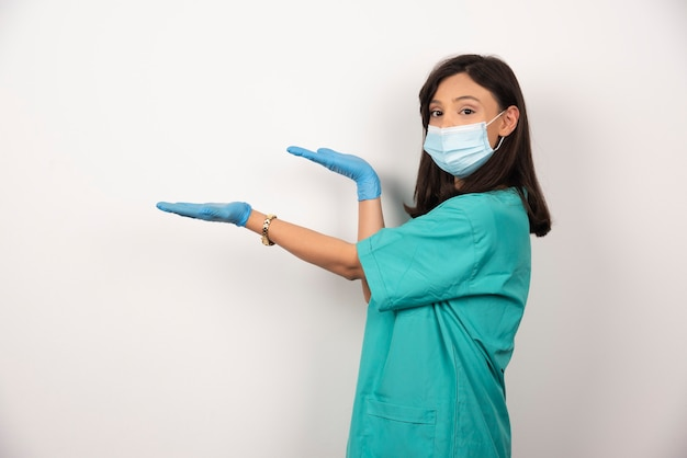 Jovem médico em máscara médica e luvas em pé sobre fundo branco. foto de alta qualidade