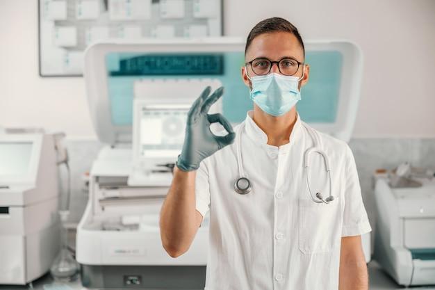 Jovem médico em pé no hospital e mostrando-se bem. o vírus corona está caindo.