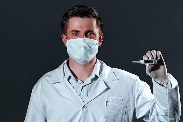 Jovem médico em um jaleco branco e máscara médica detém um termômetro eletrônico isolado no preto.