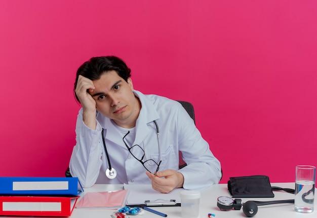 Jovem médico entediado, vestindo túnica médica e estetoscópio, sentado à mesa com ferramentas médicas, segurando óculos tocando a cabeça isolada na parede rosa