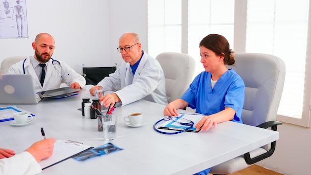 Jovem médico especialista falando com a equipe médica na sala de conferências, segurando uma radiografia, aconselhando um colega de trabalho. terapeuta clínico discutindo com colegas sobre doenças, profissional de medicina