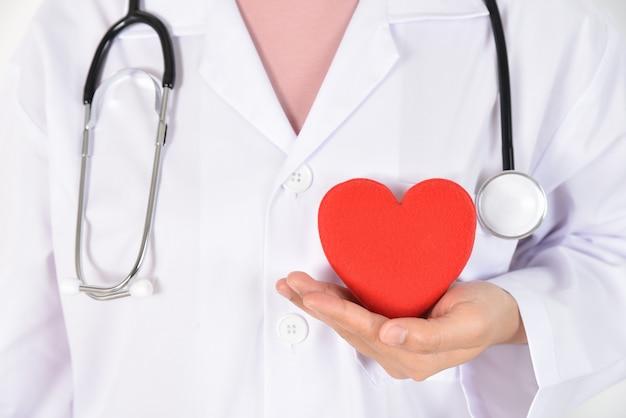 Jovem médico feminino com estetoscópio segurando coração vermelho na mão dela.