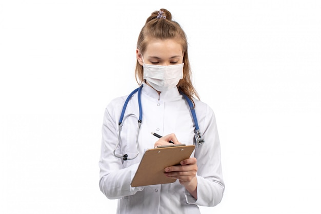 Jovem médico feminino em traje médico branco com estetoscópio em máscara protetora branca, anotando notas em branco