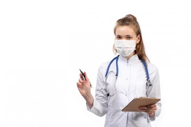Jovem médico feminino em traje médico branco com estetoscópio em máscara protetora em branco no branco