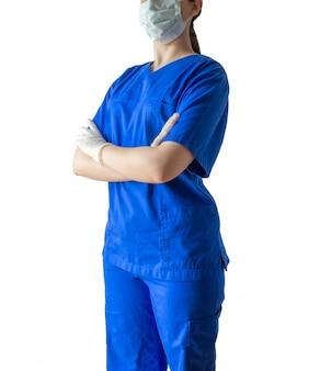 Jovem médico feminino em um uniforme médico azul em pé com confiança com as mãos cruzadas