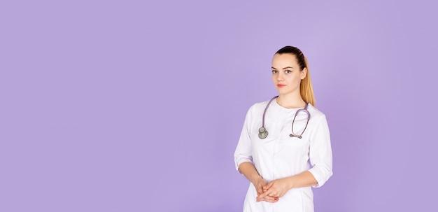 Jovem médico feminino em uniforme branco com estetoscópio no pescoço