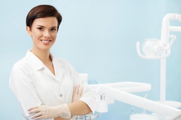 Jovem médico feminino no consultório do dentista. bela mulher sorridente no jaleco branco. clinica odontológica. estomatologia