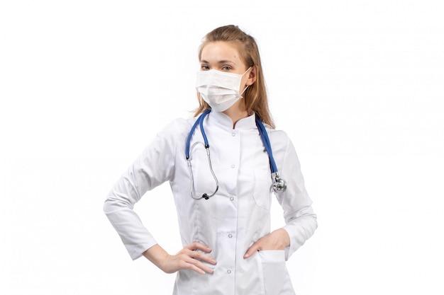 Jovem médico feminino no terno médico branco no estetoscópio de máscara protetora branco posando no branco