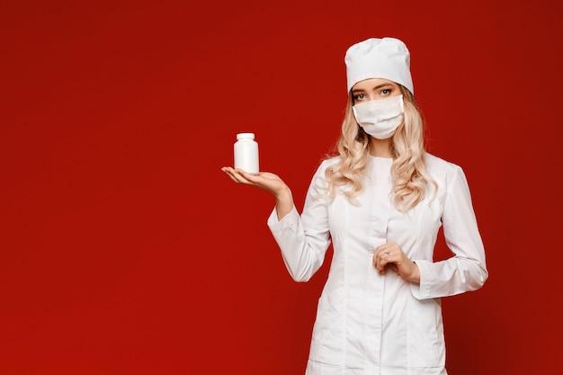 Jovem médico feminino ou enfermeira posando com frasco de comprimidos na palma da mão aberta, isolado no fundo vermelho. proteção contra vírus e conceito de saúde