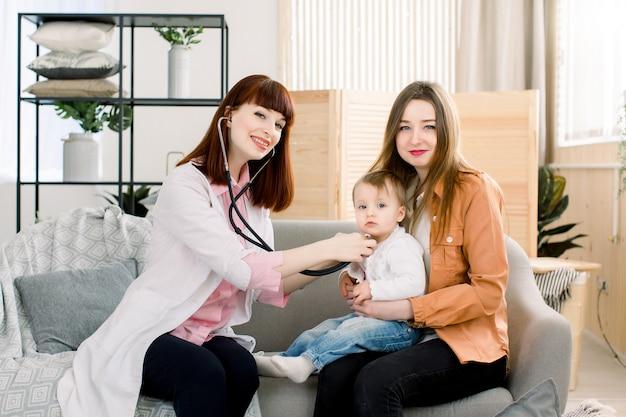 Jovem médico feminino sorridente, examinando o bebê pequeno nos braços da mãe em casa
