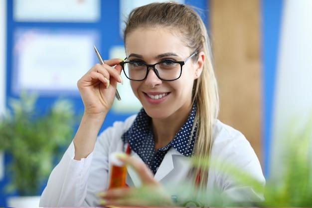 Jovem médico feminino sorridente tem medicamento na mão