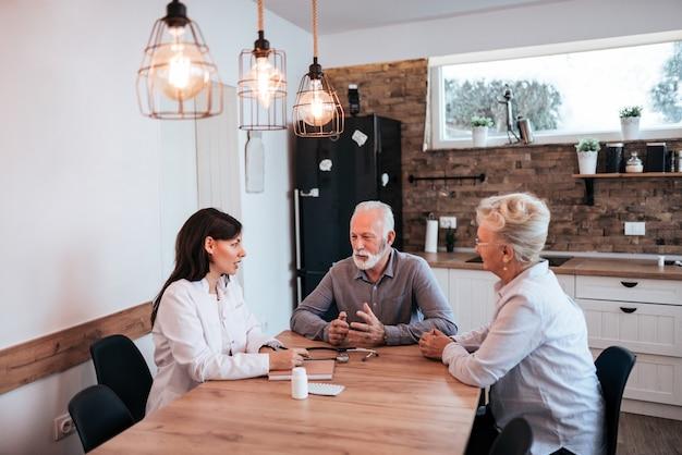 Jovem médico feminino tendo consulta com alguns idosos.