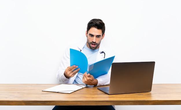 Jovem médico homem com seu laptop
