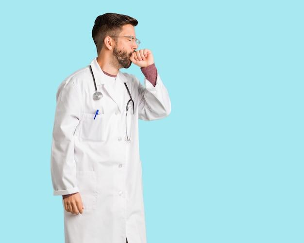 Jovem médico homem tosse, doente devido a um vírus ou infecção