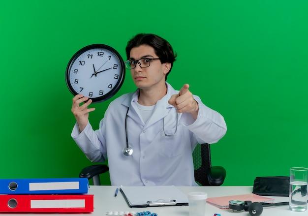 Jovem médico impressionado vestindo túnica médica e estetoscópio com óculos, sentado à mesa com ferramentas médicas, segurando um relógio, olhando e apontando isolado na parede verde