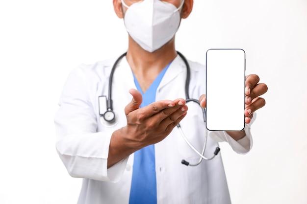 Jovem médico indiano mostrando a tela do smartphone sobre fundo branco.