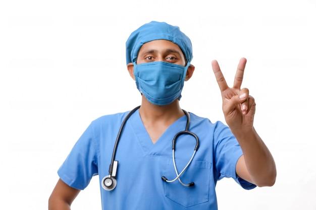 Jovem médico indiano mostrando sinal de vitória sobre fundo branco.