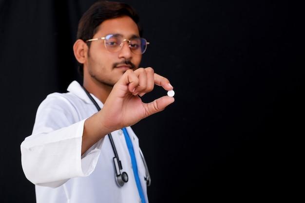 Jovem médico indiano segurando a pílula na mão.