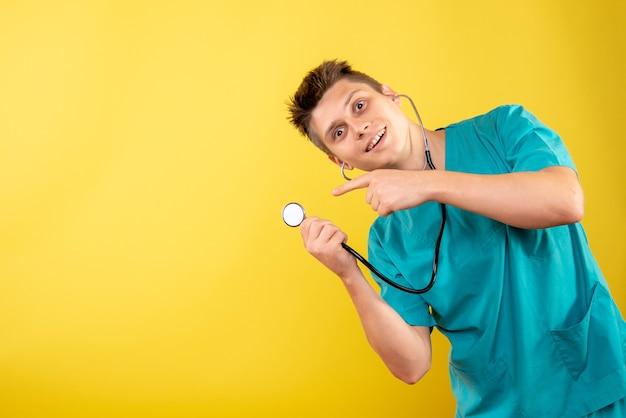 Jovem médico masculino de frente para o terno médico com estetoscópio sobre fundo amarelo