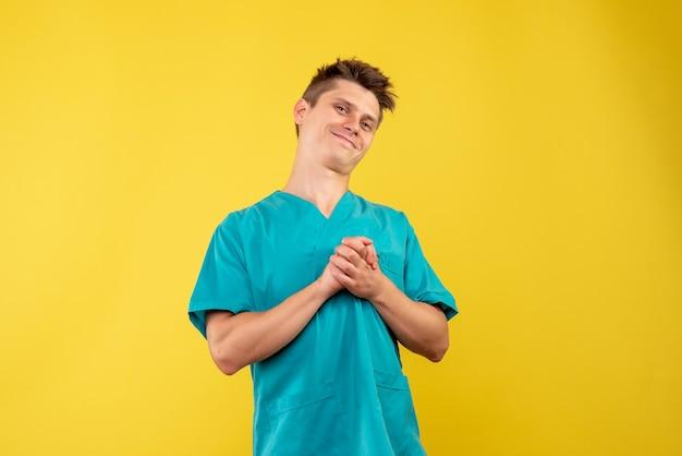 Jovem médico masculino de frente para o terno médico em fundo amarelo