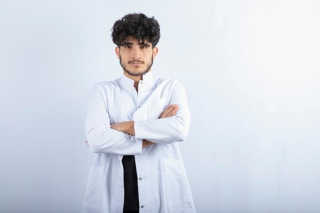 Jovem médico masculino em pé na parede branca.