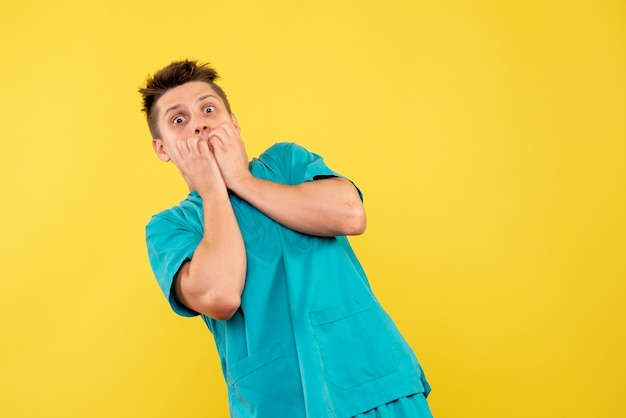 Jovem médico masculino em terno médico assustado com um fundo amarelo.