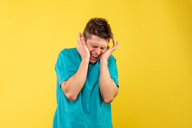 Jovem médico masculino em terno médico com orelhas fechadas em fundo amarelo.