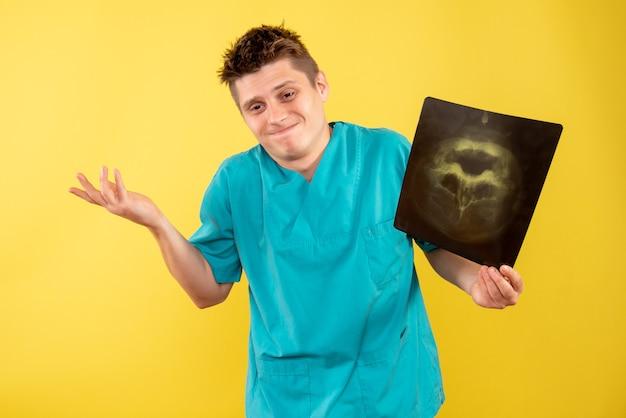 Jovem médico masculino em terno médico segurando um raio-x em fundo amarelo de frente