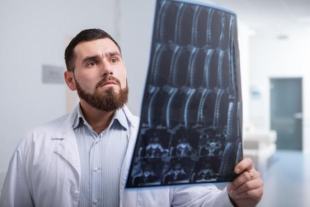 Jovem médico masculino examinando a ressonância magnética de um paciente, trabalhando em uma clínica moderna