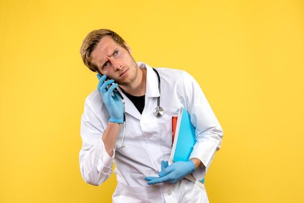 Jovem médico masculino falando no telefone sobre fundo amarelo.