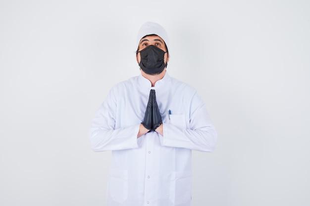 Jovem médico masculino mostrando gesto namastê em uniforme branco e parecendo calmo. vista frontal.