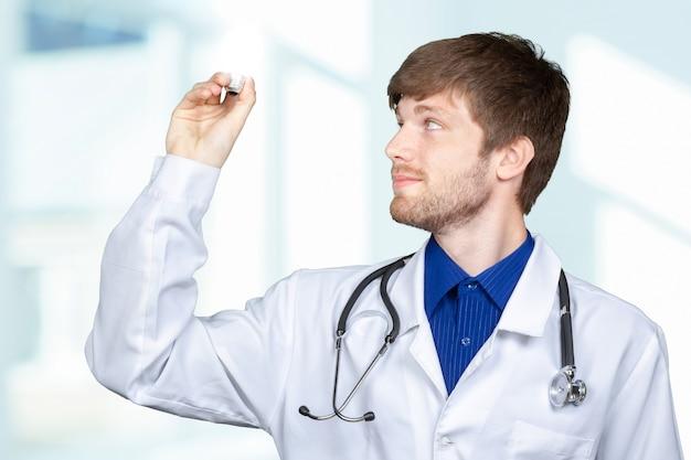 Jovem médico masculino no jaleco branco e estetoscópio segurando a lâmpada.