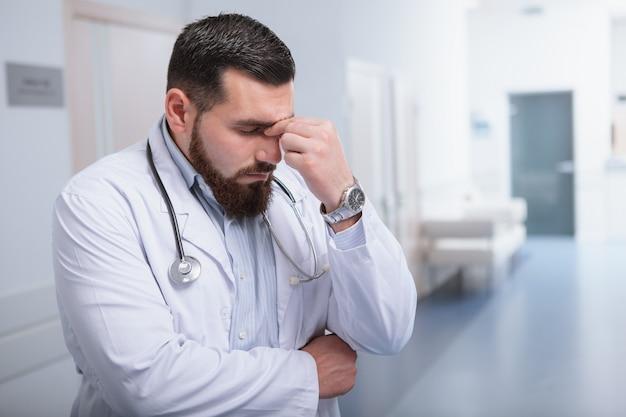 Jovem médico masculino, olhando cansado, em pé no corredor do hospital