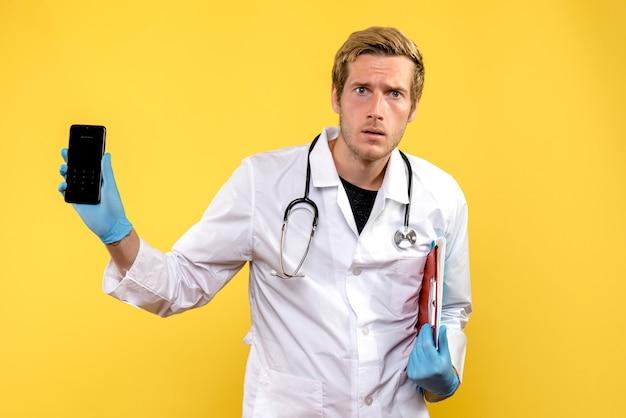 Jovem médico masculino segurando o telefone no fundo amarelo saúde médico humano de frente