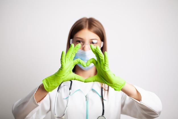 Jovem médico mostra um símbolo do coração em luvas