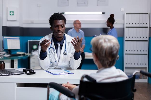 Jovem médico negro falando com paciente inválido na mesa do consultório