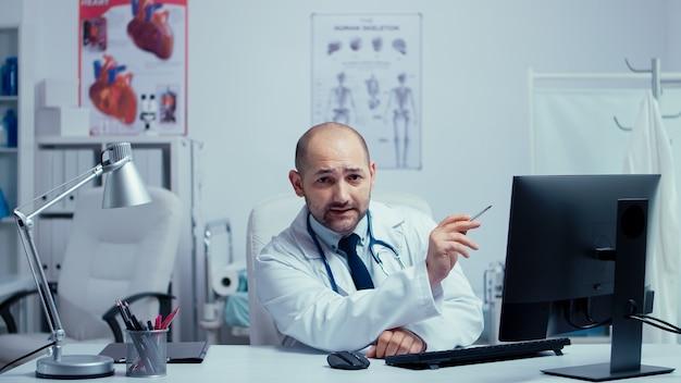 Jovem médico oferecendo aconselhamento médico na internet no consultório de um hospital de clínica privada moderna. médico usando tecnologia da internet para consultar pacientes durante a pandemia global covid-19. telemedicina e saúde