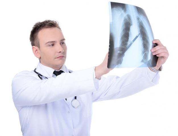Jovem médico olhando para raio-x, isolado