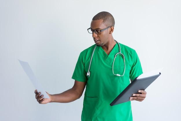Jovem médico olhando para resultados de exames médicos.