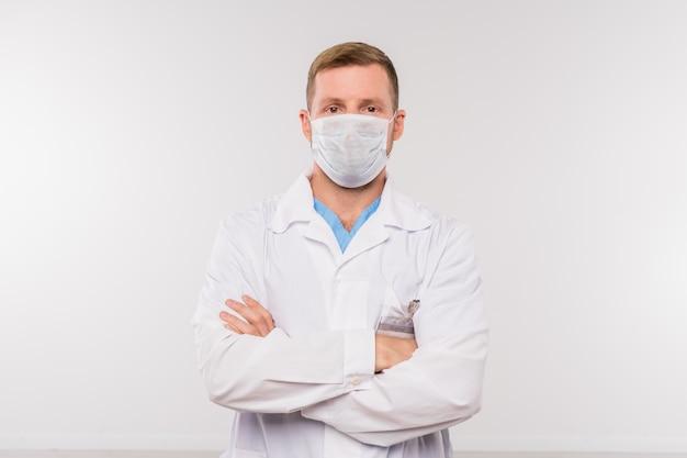 Jovem médico ou cirurgião em jaleco branco e máscara protetora cruzando os braços no peito enquanto olha para você isolado