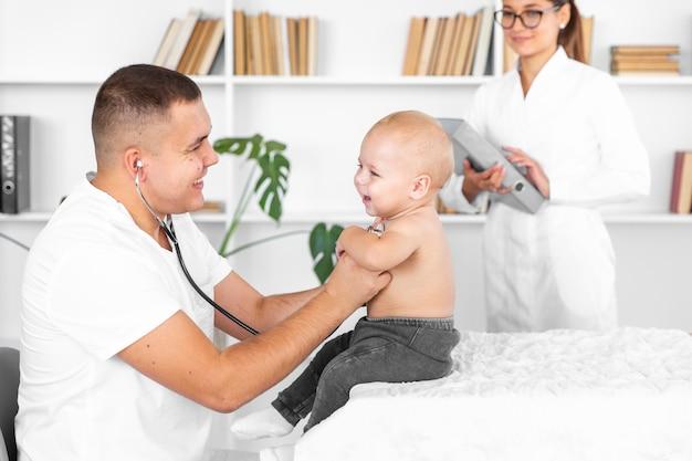 Jovem médico ouvindo bebê adorável com estetoscópio