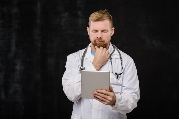 Jovem médico pensativo, de jaleco branco e estetoscópio no pescoço, olhando dados on-line em um tablet sobre fundo preto