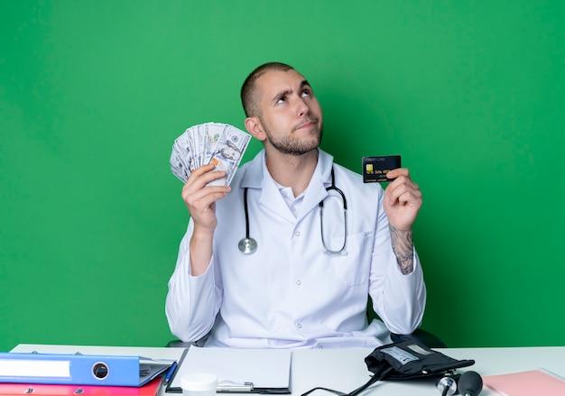 Jovem médico pensativo, vestindo túnica médica e estetoscópio, sentado à mesa com ferramentas de trabalho, segurando dinheiro e cartão de crédito, olhando para cima isolado na parede verde