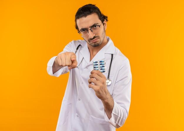 Jovem médico rigoroso com óculos médicos, usando roupão médico com estetoscópio segurando pílulas e mostrando seu gesto em amarelo